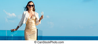 Woman drinking sparkling wine looking over ocean