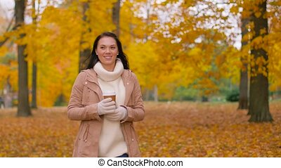 woman drinking takeaway coffee in autumn park - season, hot...