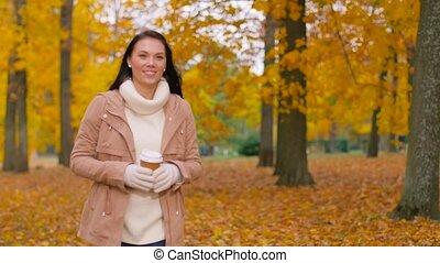 woman drinking takeaway coffee in autumn park - season, hot...
