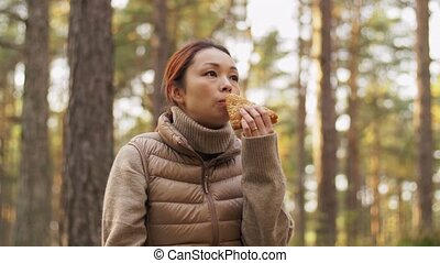 picking season, leisure and people concept - young asian woman in basket drinking tea and eating sandwich in autumn