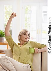 Woman drinking tea and stretching at home