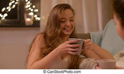 woman drinking tea and talking to friend at home -...