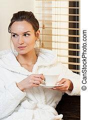 Woman drinking tea before treatment