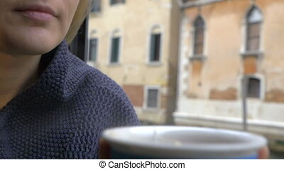 Woman drinking tea by the window with Venice view
