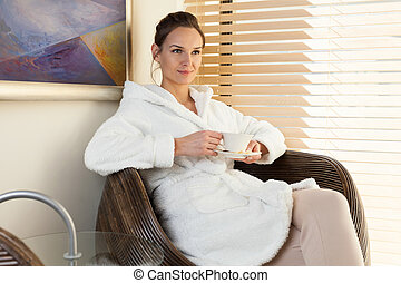Woman drinking tea in waiting room at spa center