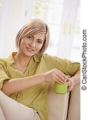 Woman drinking tea on couch at home