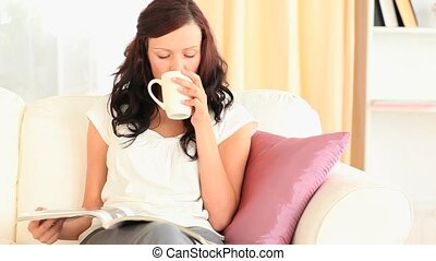 Woman drinking tea while reading a