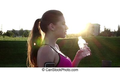 Woman drinking water after a fitness run. Slow motion