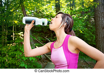 Woman Drinking Water after a Workout Outdoors