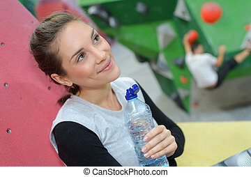 woman drinking water after climbing exercise