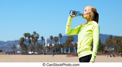 woman drinking water after doing sports outdoors