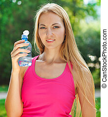 Woman drinking water after fitness exercise
