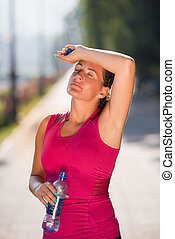woman drinking water from a bottle after jogging