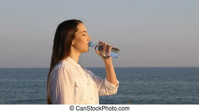 Woman drinking water from a bottle on the beach - Side view...