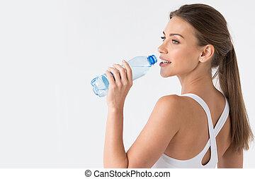 Woman drinking water from blue bottle - Beautiful fit woman...