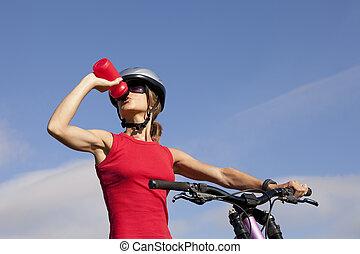 Woman drinking water in her bike