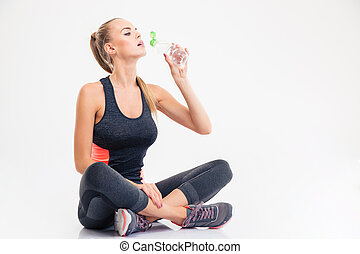 Woman drinking water - Woman sitting on the floor and...