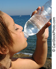 Woman drinking water - Young woman drinking water at the...