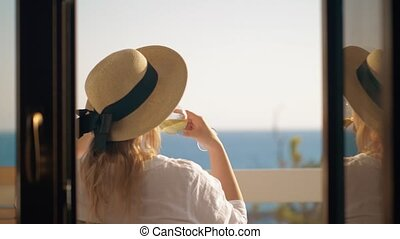 Woman drinking wine and relaxing at the balcony overlooking sea