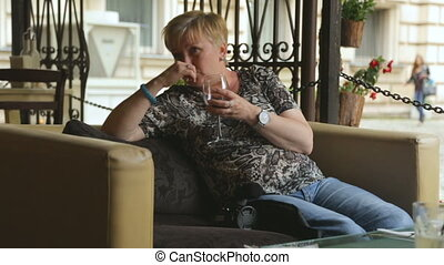 Woman drinking wine in street cafe
