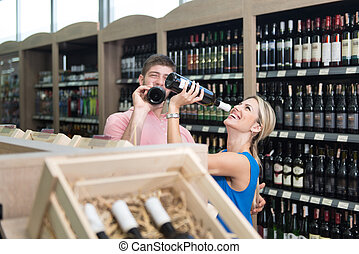 Woman Drinking Wine In Supermarket - Beautiful Young Couple...
