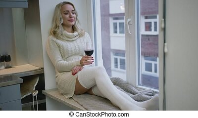 Woman drinking wine near window