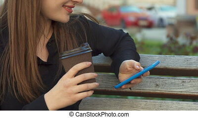 Woman drinks coffee on the bench