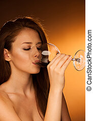 woman drinks glass of red wine