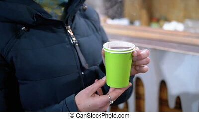 Woman Drinks Mulled Wine from a Plastic Cup while Standing on the Street in Winter