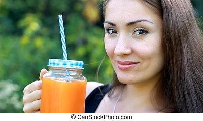 Woman drinks smoothies or orange fresh outdoors.Closeup...
