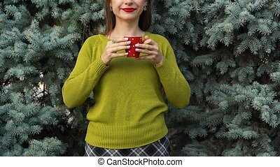 Woman drinks tea or coffee from a red cup on the background of pine branches