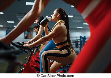 Woman drinks water on a stationary bike in gym