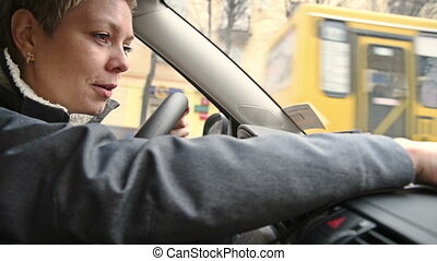 Woman driver programming the GPS navigator in car