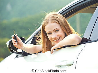 woman driver with keys driving a new car - happy woman...