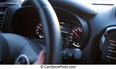 closeup of hand on the steering wheel and speedometer