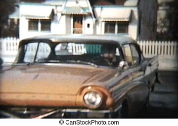 A woman backs her salmon colored 1957 Ford Meteor out of the driveway and heads off to do some shopping. (Scan from archival 8mm film)