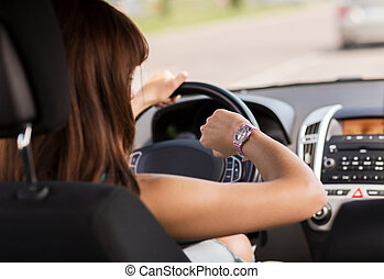 woman driving a car and looking at watch - transportation...