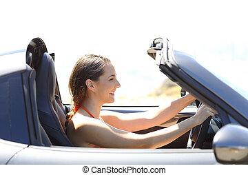 Woman driving a convertible car on summer vacation
