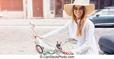 Woman driving a scooter in the city street.