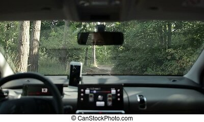 Woman driving car on ground road in the forest