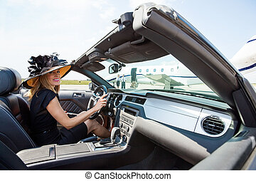 Woman Driving Convertible Towards Private Jet At Terminal