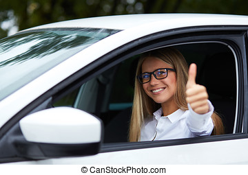 Woman driving his car and makes gesture with thumb up