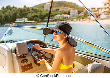 Woman driving yacht - Young and pretty woman in yellow skirt...