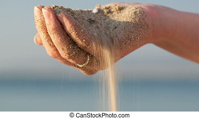 Close up of the hand of a woman drizzling sea sand through her fingers against an ocean backdrop, conceptual image