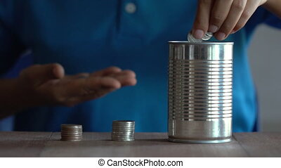 Woman drop a coin into a old can.