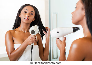 Woman drying hair. Rear view of beautiful young African woman washing hands in bathroom and looking at the mirror