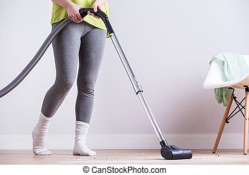 Woman dusting dirty apartment