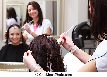Woman dying hair in hairdressing beauty salon. By hairstylist.