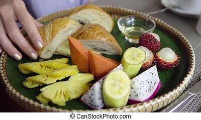 Woman eat morning breakfast with tropical fruit, croissant, pancake and honey.