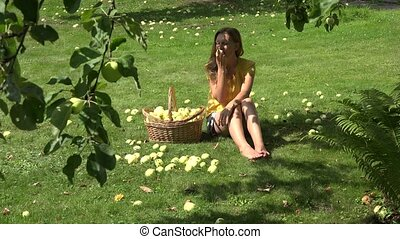 woman eat ripe apple sitting on grass in orchard at summer. 4K